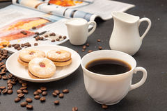 Coffee break. Morning breakfast. Cup of coffee and cookies. Cup of coffee, saucer with cookies, milk jug, roasted coffee beans and culinary magazin over on dark Stock Images