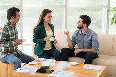 Coffee break. Multi-ethnic business team having coffee break in the office Stock Images