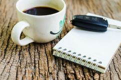 Coffee break,Notebook and coffee cup on wooden board Royalty Free Stock Photography