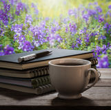 Coffee break with notebooks and pen on wooden table in the garde Stock Photos