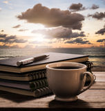 Coffee break with notebooks and pen on wooden table with view of Royalty Free Stock Photos