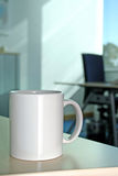 Coffee break at the office. A white mug over a table in a office stock photos