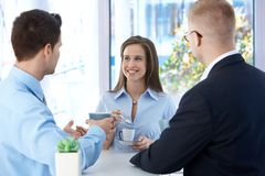 Coffee break in office. Coworkers enjoying free time and conversation, smiling Royalty Free Stock Images