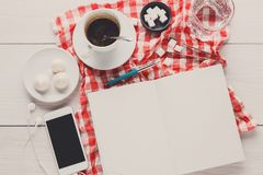 Coffee cup and smartphone on checkered cloth at white wood Stock Photography