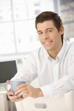 Coffee break in office, smiling businessman. Sitting, holding cup, looking at camera Royalty Free Stock Images