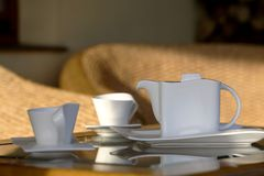 Coffee Break On Patio. Pitcher and cups for coffee sitting on a table near patio furniture on an outdoor patio stock image
