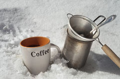 Coffee Break On Snow. Cup of fresh made coffee next to a coffee maker and drainer. All placed on the snow Stock Photo