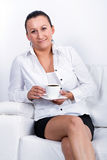 Coffee break  on the sofa. Beautiful brunette at coffee break on the sofa Royalty Free Stock Photos