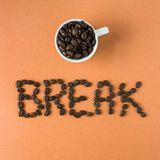 Coffee break spelled out in beans with an espresso cup. Overhead view of message written in coffee beans Royalty Free Stock Photo