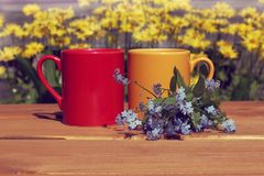 Coffee break with a summer mood. Red and orange mug with a blue bouquet of flowers on a street table Royalty Free Stock Photos