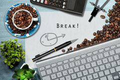 Coffee Break Time in Office. Desk with a coffee cup with roasted coffee beans, computer keyboard, pencil, calculator and drawing compass Royalty Free Stock Image