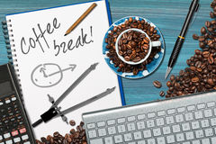 Coffee Break Time in Office. Desk with a coffee cup with roasted coffee beans, computer keyboard, pencil, calculator and drawing compass Royalty Free Stock Images