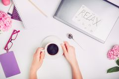 Coffee break time on the workspace - female hands with cup of coffee on the white working office desk with laptop, notebook, glass royalty free stock photos