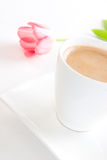 Coffee break with a tulip. A cup of creamy black coffee on a square saucer with a pink tulip and green leaf in the background Stock Photos