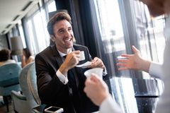 Coffee break. Two cheerful business men talking in a restaurant stock image