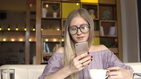 Coffee break. Woman using smartphone and smiling