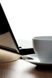 Coffee break at work. Coffee cup and laptop in background. Royalty Free Stock Photography