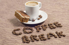 Coffee Break Written in coffee Beans. Words coffee Break written in whole coffee beans with a cup of coffee and cappuccino cake on the side Stock Photos
