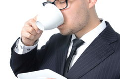 Coffee break. Young man in suit drinking coffee isolated Stock Photography