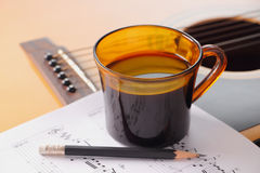 Coffee break for your guitar practice. Cup of black coffee with music notes and pencil on acoustic guitar Royalty Free Stock Image