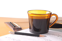 Coffee break for your guitar practice. Cup of black coffee with music notes and pencil on acoustic guitar Stock Image