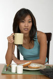 Coffee at breakfast. Woman with coffee and bagle at computer Stock Photography