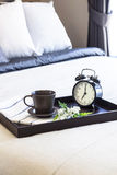 Coffee Breakfast set in Bedroom with Alarm clock. And flower in wooden tray Royalty Free Stock Images