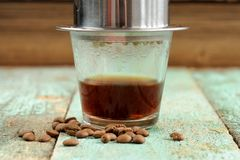 Coffee brewed in small metal French drip filter on wooden table Stock Images