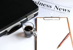 Coffee and briefcase with notebook on newpaper. royalty free stock images