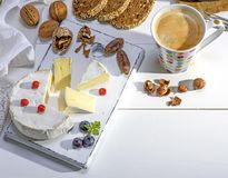 Coffee with brown foam in a white ceramic mug in colorful polka-. Dot, and a round camembert cheese , breakfas Stock Photo