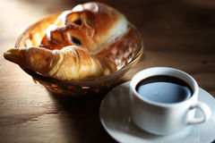Coffee and bun. On wooden table with mood lighting stock photos