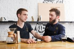 Male bartenders brewing fresh coffee at cafe interior. Coffee business backgroung with copy space. Portrait of two bartenders preparing bracing drink in chemeks Stock Images