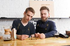 Male bartenders brewing fresh coffee at cafe interior. Coffee business backgroung with copy space. Portrait of two bartenders preparing bracing drink in chemeks Royalty Free Stock Photography