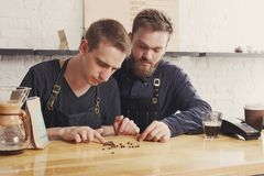 Male bartenders brewing fresh coffee at cafe. Coffee business backgroung with copy space. Portrait of two bartenders preparing bracing drink in chemeks and Royalty Free Stock Image