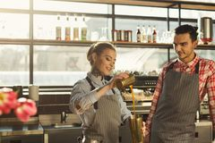 Male and female bartenders brewing fresh coffee at cafe interior. Coffee business backgroung with copy space. Portrait of two young bartenders preparing fresh Royalty Free Stock Photos
