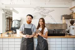 Coffee Business Concept - happy young bartender baristas ready to give service at modern coffee shop. Coffee Business Concept - happy young bartender baristas Stock Photo