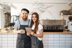 Coffee business concept - happy young couple business owners of small coffee shop working and planing on tablet. stock photo