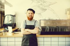 Coffee Business Concept - Positive young bearded man in apron looking at camera while standing at bar Counter.  Royalty Free Stock Image
