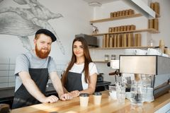 Coffee Business Concept - Positive young bearded man and beautiful attractive lady barista couple in apron looking at royalty free stock photo