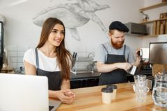 Coffee Business Concept - Positive young bearded man and beautiful attractive lady barista couple enjoy working together Stock Photos