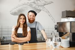 Coffee Business Concept - Positive young bearded man and beautiful attractive lady barista couple enjoy working together Stock Image