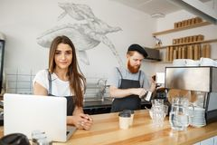 Coffee Business Concept - Positive young bearded man and beautiful attractive lady barista couple enjoy working together Royalty Free Stock Photos