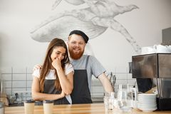 Coffee Business Concept - Positive young bearded man and beautiful attractive lady barista couple enjoy working together Stock Images
