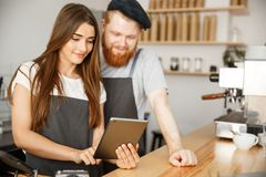 Coffee business concept - satisfied and smile owners couple look on tablet orders online in modern coffee shop.  Royalty Free Stock Photos