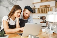Coffee Business Concept - Satisfied and smile owners look on laptop for online orders at coffee shop.  Royalty Free Stock Photos