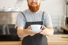 Coffee business owner concept - portrait of happy young bearded caucasian barista in apron with confident looking. Servicing hot coffee to customer in coffee Royalty Free Stock Images