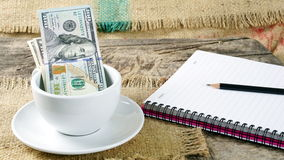Coffee Business. Some money in coffee cup on the wood table with pencils and notebook, they mean profit or business of coffee Stock Image