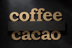 Coffee and cacao letters on black Stock Photos