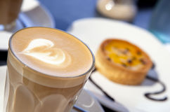 Coffee and Cake. A frothy latte coffee, with a passionfruit tart in the background Stock Images