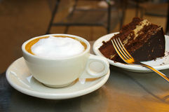 Coffee and cake. Cappuccino coffee and chocolate cake royalty free stock image